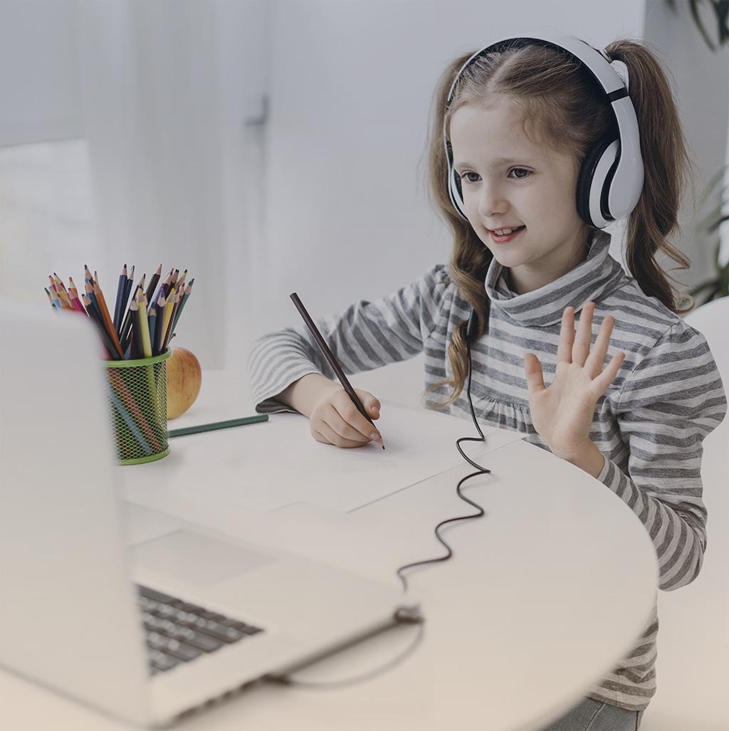 Niña saludando a un computador