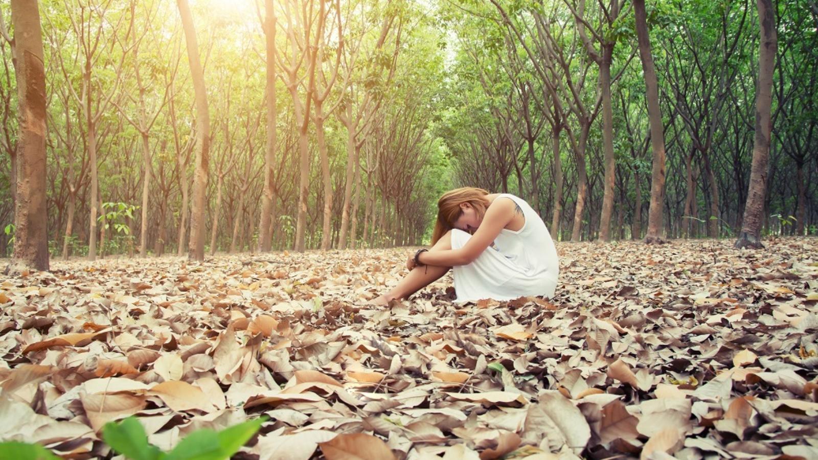 Mujer asiática joven tristemente sentado en la hoja seca en el bosque solo