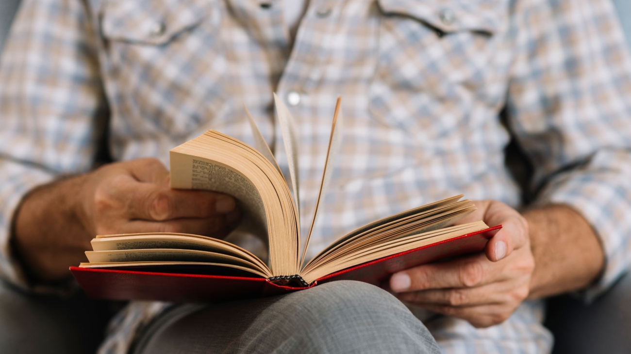 mid-section-man-turning-pages-book
