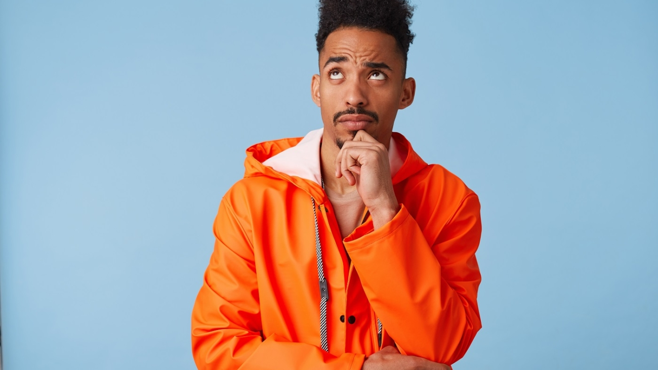Portrait of young african american dark skinned man in orange rain coat, holds his chin, looks up and thinks about plans for the future stands over blue background.