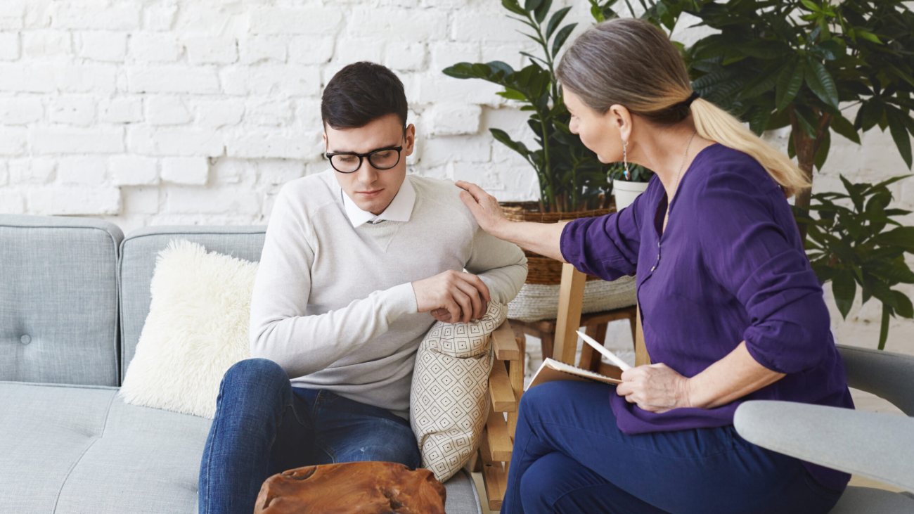 Candid shot of casually dressed professional woman psychotherapist in her fifties touching her young male patient by shoulder while having counseling session, expressing sympathy and support