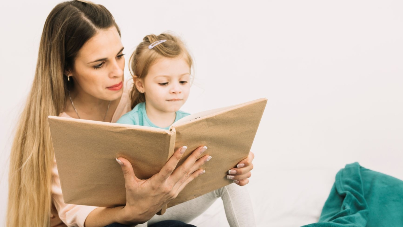 mother-reading-book-cute-girl-bed (1)m
