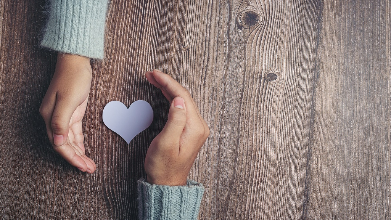 paper heart and couple's hands on wooden table