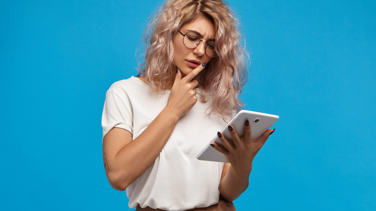 Thoughtful young attractive woman surfing internet reading world news or checking email on digital tablet. Pensive cute girl in eyewear using generic touch pad portable computer for remote work