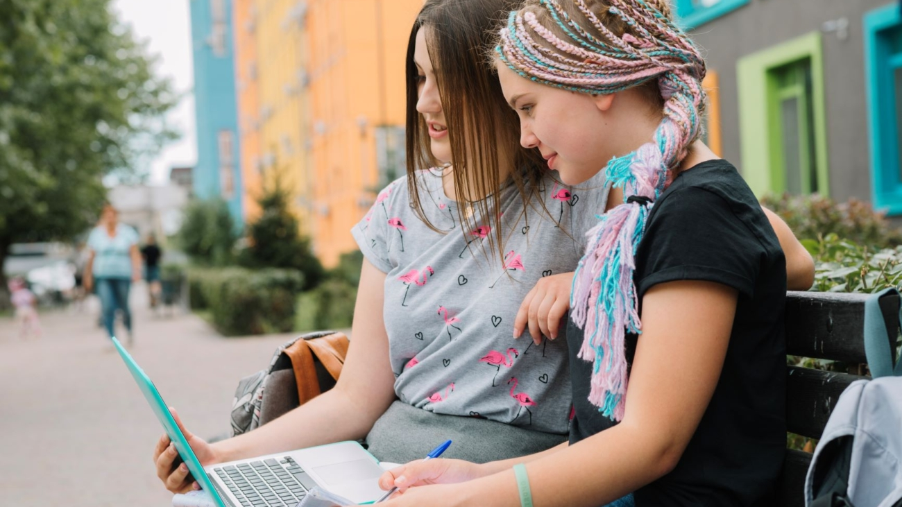 stylish-girls-studying-with-laptop-at-street