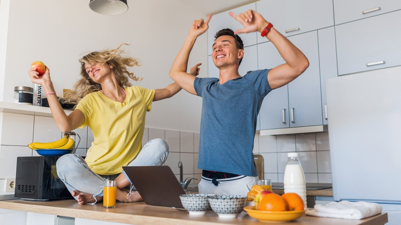 young attractive couple of man and woman cooking breakfast together in morning at kitchen, happy family, romantic, healthy food, freeelancer at work on laptop, dancing to music, having fun, laughing